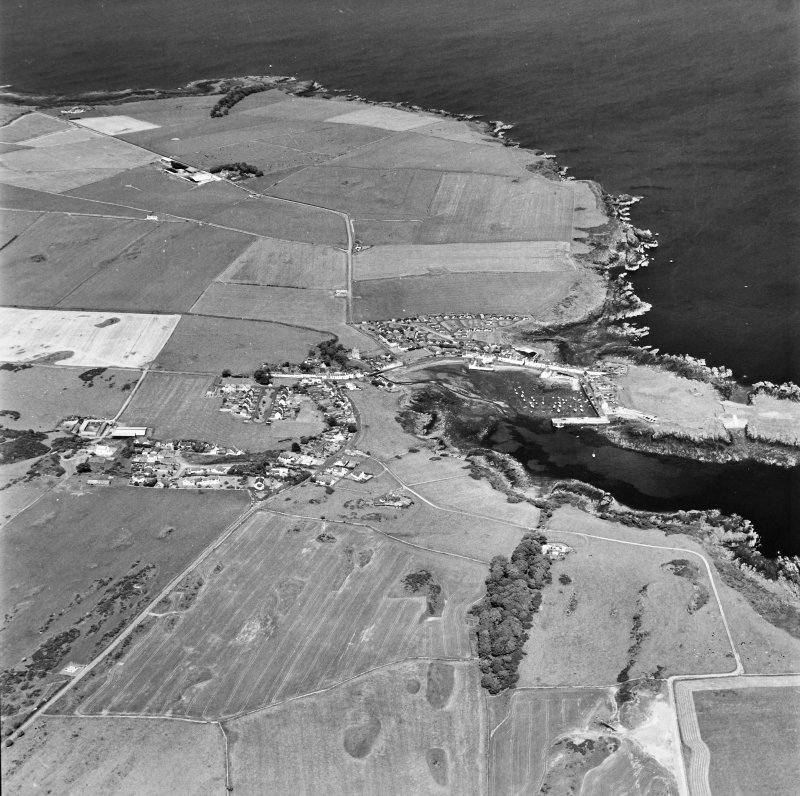 Oblique aerial view, taken from the WSW, centred on the village and harbour, and showing the remains of St. Ninian's Chapel in the centre right of the photograph.