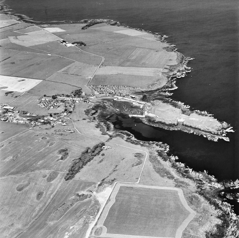 Oblique aerial view, taken from the SW, centred on the village and harbour, and showing Isle Head fort and the remains of St. Ninian's Chapel in the centre right of the photograph.