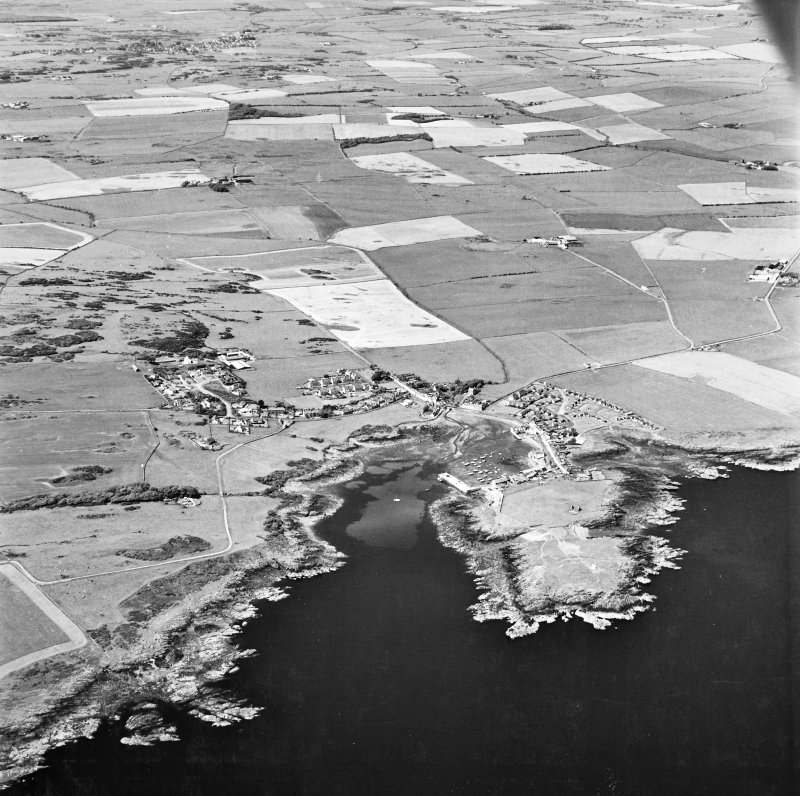 Oblique aerial view, taken from the SSE, centred on the village and harbour, Isle Head fort and the remains of St. Ninian's Chapel.
