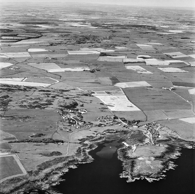 Oblique aerial view, taken from the SSE, showing the village and harbour, Isle Head fort and the remains of St. Ninian's Chapel in the bottom right-hand corner of the photograph.