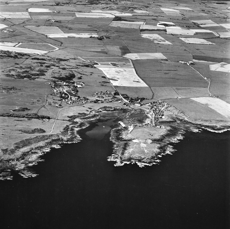 Oblique aerial view, taken from the S, centred on the village and harbour, Isle Head fort and the remains of St. Ninian's Chapel.