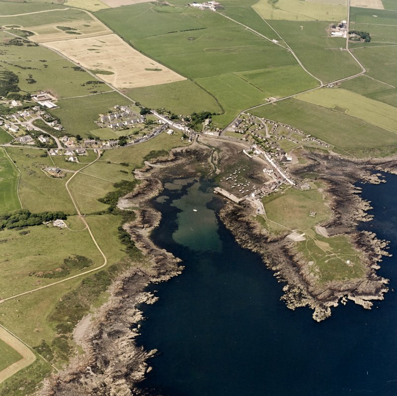 Oblique aerial view, taken from the S, centred on the village and harbour, and showing Isle Head fort and the remains of St. Ninian's Chapel in the bottom right-hand corner of the photograph.