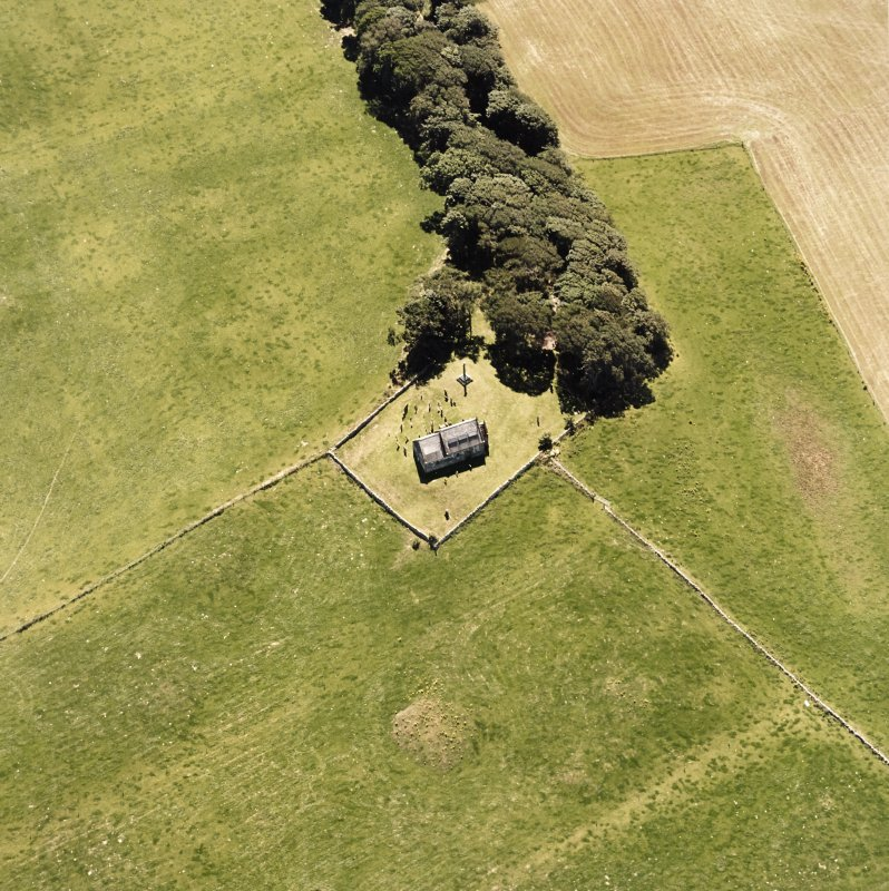 Oblique aerial view centred on the church and burial-ground, taken from the N.