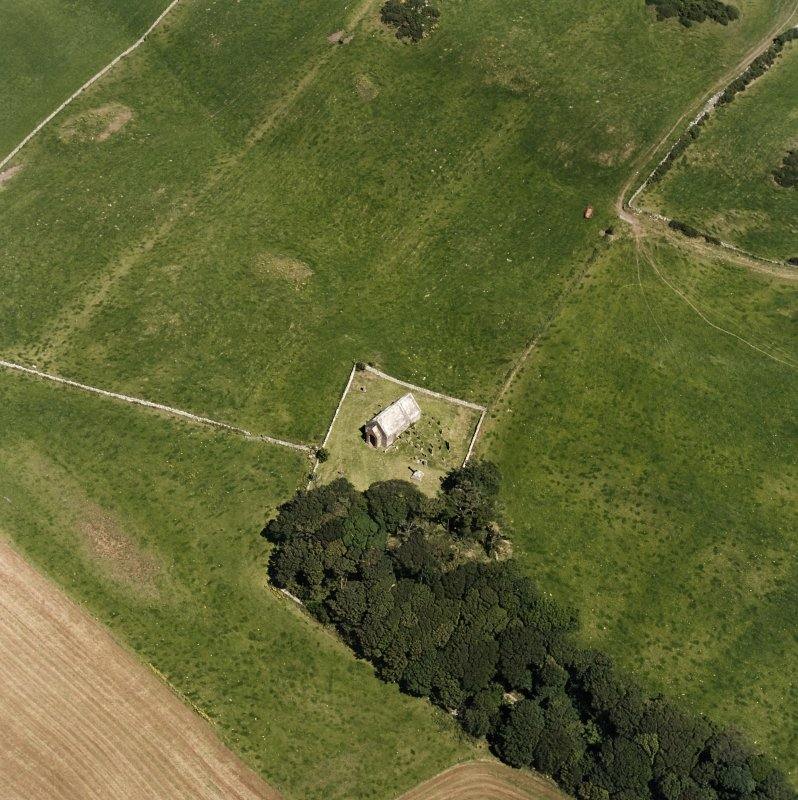 Oblique aerial view centred on the church and burial-ground, taken from the SW.