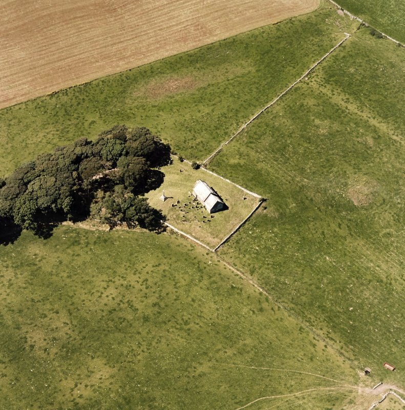 Oblique aerial view centred on the church and burial-ground, taken from the E.