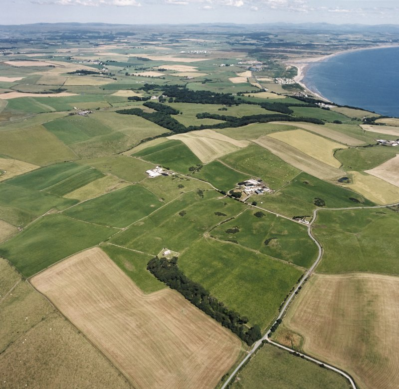 General oblique aerial view looking across the church and burial ground towards Stoneykirk and Luce Bay, taken from the SSW.