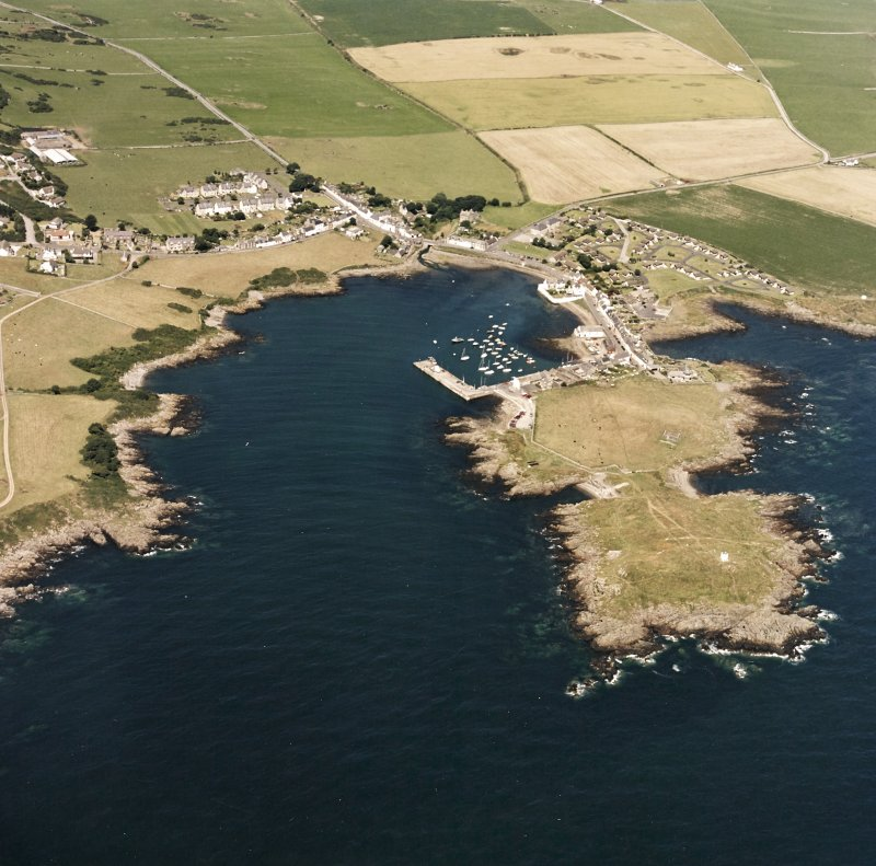 General oblique aerial view centred on the village, harbour, and the remains of the chapel and promontory fort, taken from the SSE.