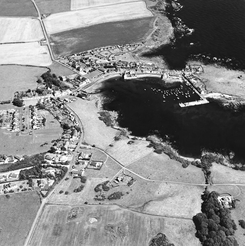 Oblique aerial view centred on the village and harbour with the remains of the chapel adjacent, taken from the SW.