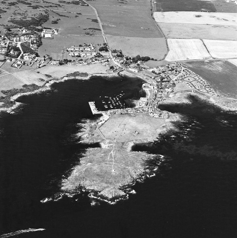 General oblique aerial view centred on the village, harbour, and the remains of the chapel and promontory fort, taken from the SE.