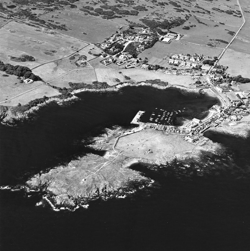 General oblique aerial view centred on the village, harbour, and the remains of the chapel and promontory fort, taken from the E.