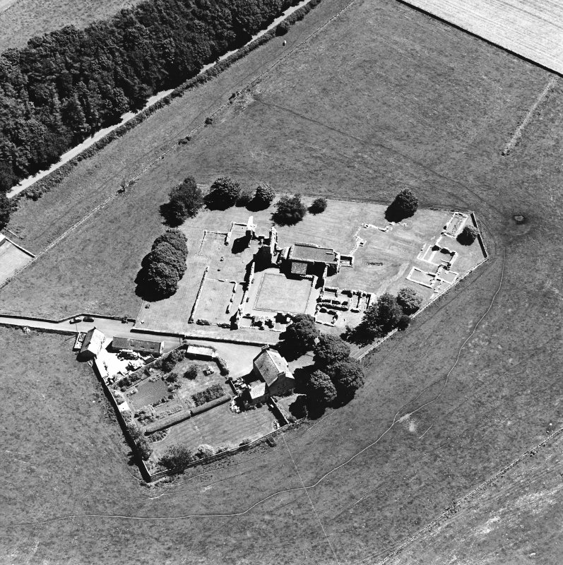 Oblique aerial view centred on the remains of the abbey and abbot¿s house, taken from the WNW.