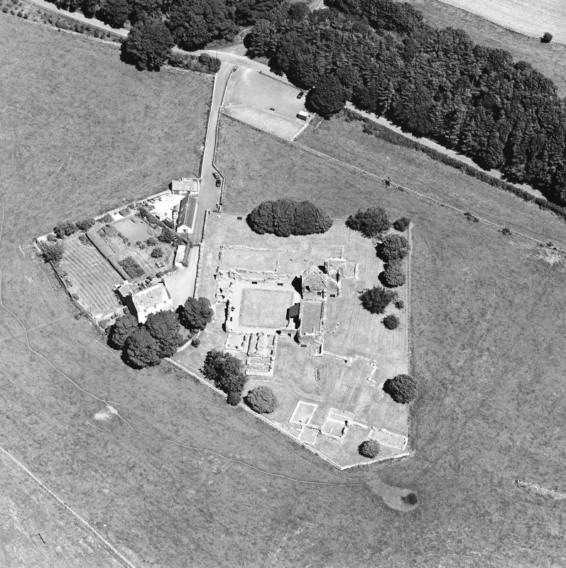 Oblique aerial view centred on the remains of the abbey and abbot¿s house, taken from the SW.