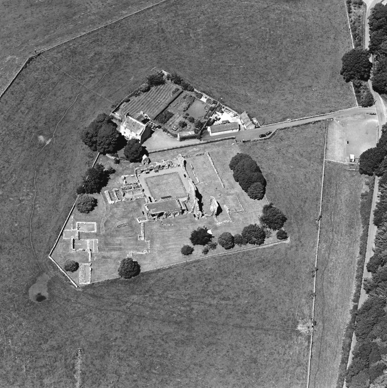 Oblique aerial view centred on the remains of the abbey and abbot¿s house, taken from the SE.
