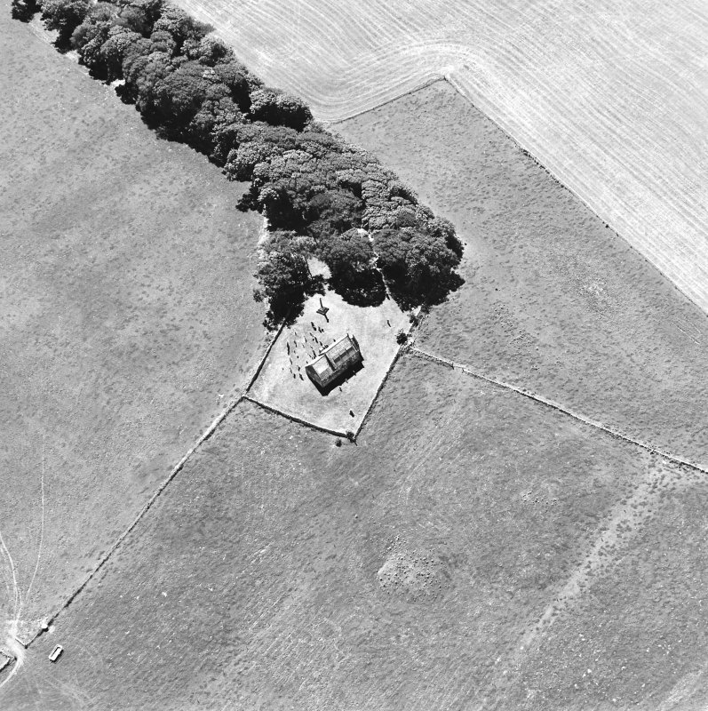 Oblique aerial view centred on the church and burial-ground, taken from the NE.