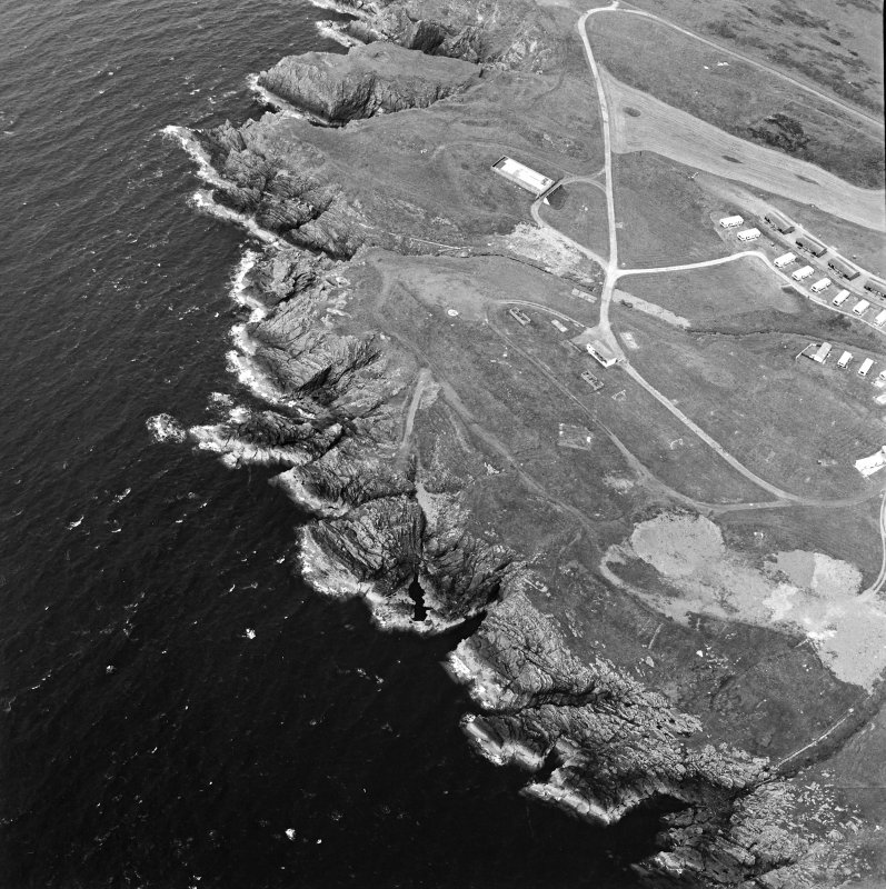 Oblique aerial view centred on the remains of the anti-aircraft battery and buildings with the remains of the promontory fort adjacent, taken from the ESE.