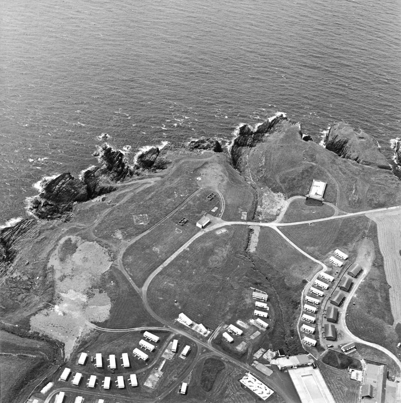 Oblique aerial view centred on the remains of the anti-aircraft battery and buildings with the remains of the promontory fort adjacent, taken from the NE.