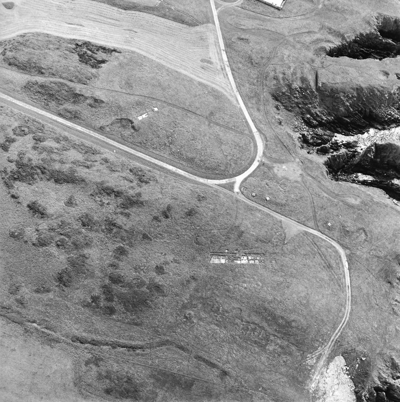 Oblique aerial view centred on the remains of buildings with the remains of the promontory fort adjacent, taken from the NW.