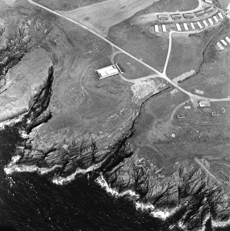 Oblique aerial view centred on the remains of the anti-aircraft battery and buildings with the remains of the promontory fort adjacent, taken from the S.