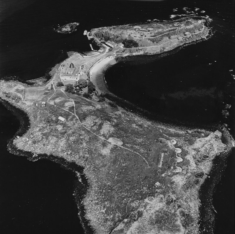 Inchcolm Island, oblique aerial view, taken from the SW, centred on a coast battery, with Inchcolm Abbey and three coastal batteries visible in the background.