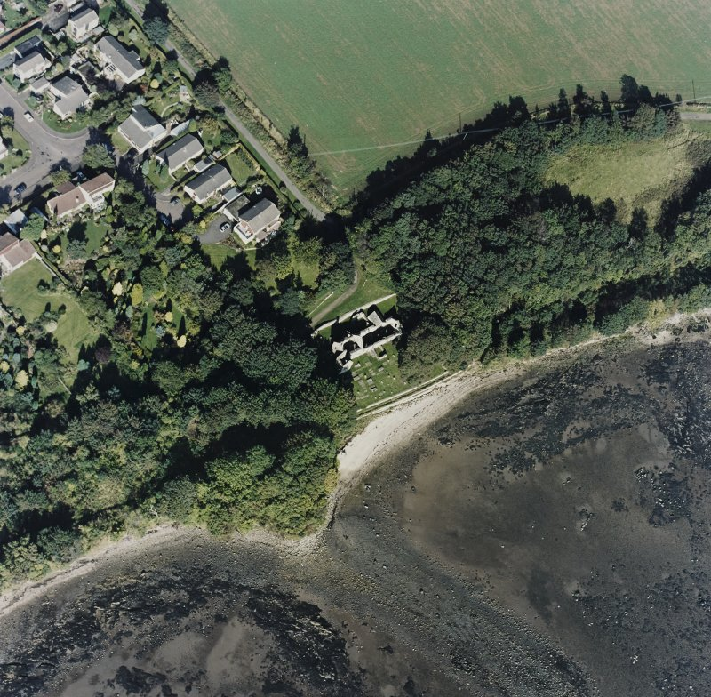 Oblique aerial view centred on the church and burial ground, with pier adjacent, taken from the SSW.
