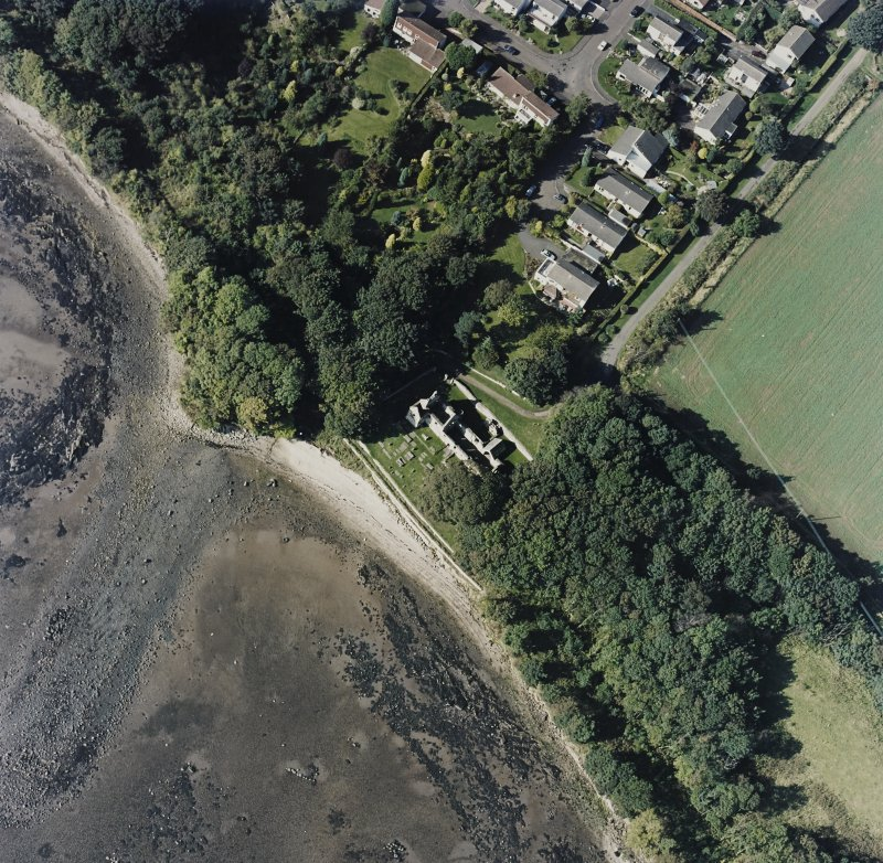 Oblique aerial view centred on the church and burial ground, with pier adjacent, taken from the SE.