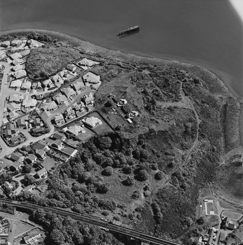 Oblique aerial view of Carlingnose point centred on the remains of a battery and submarine mining station, taken from the WSW.