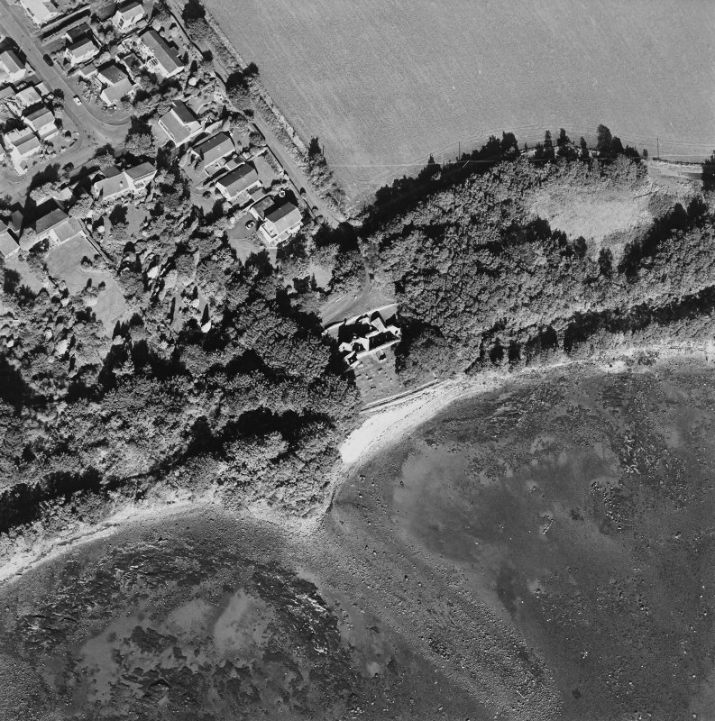 Oblique aerial view centred on the church and burial ground with pier adjacent, taken from the S.