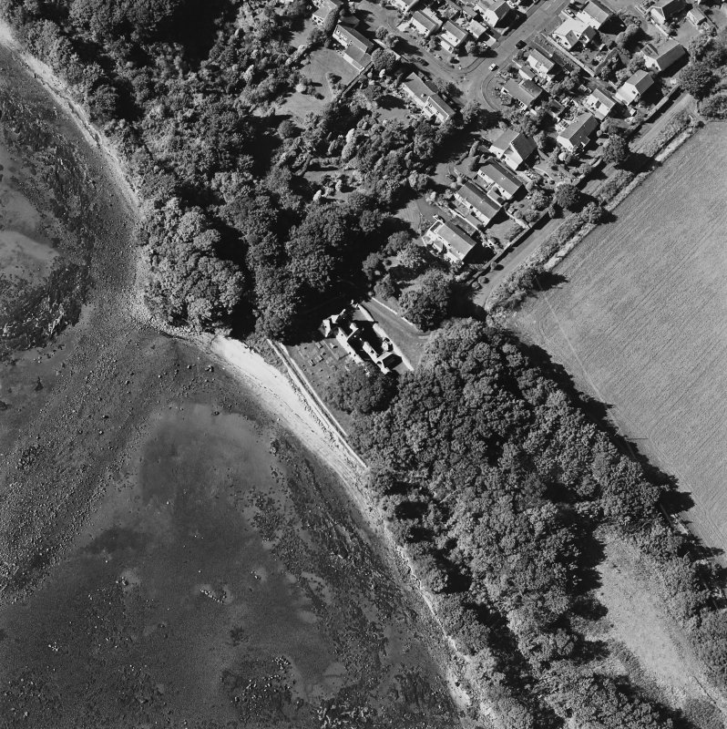 Oblique aerial view centred on the church and burial ground with pier adjacent, taken from the ESE.