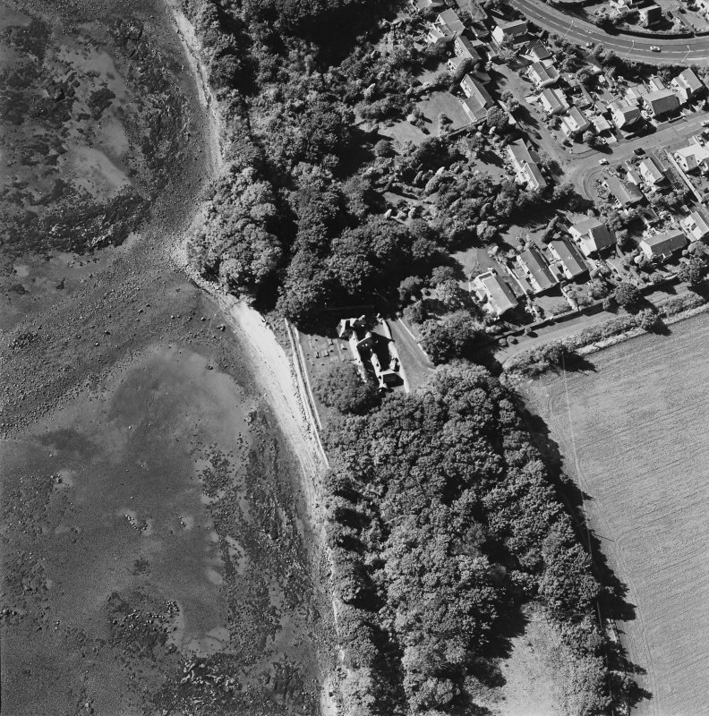 Oblique aerial view centred on the church and burial ground with pier adjacent, taken from the E.