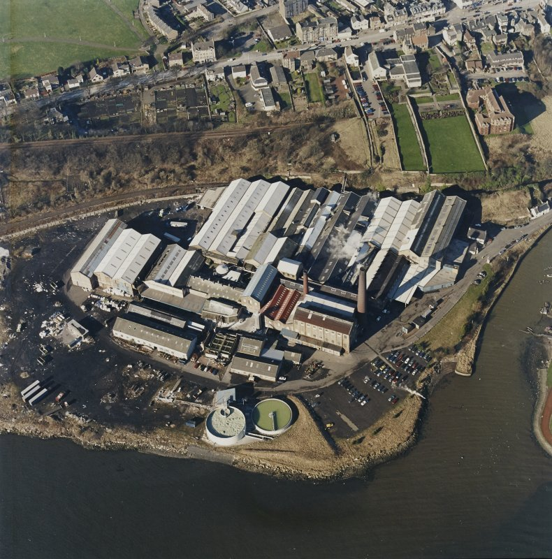 Oblique aerial view centred on the paper mill, taken from the SE.