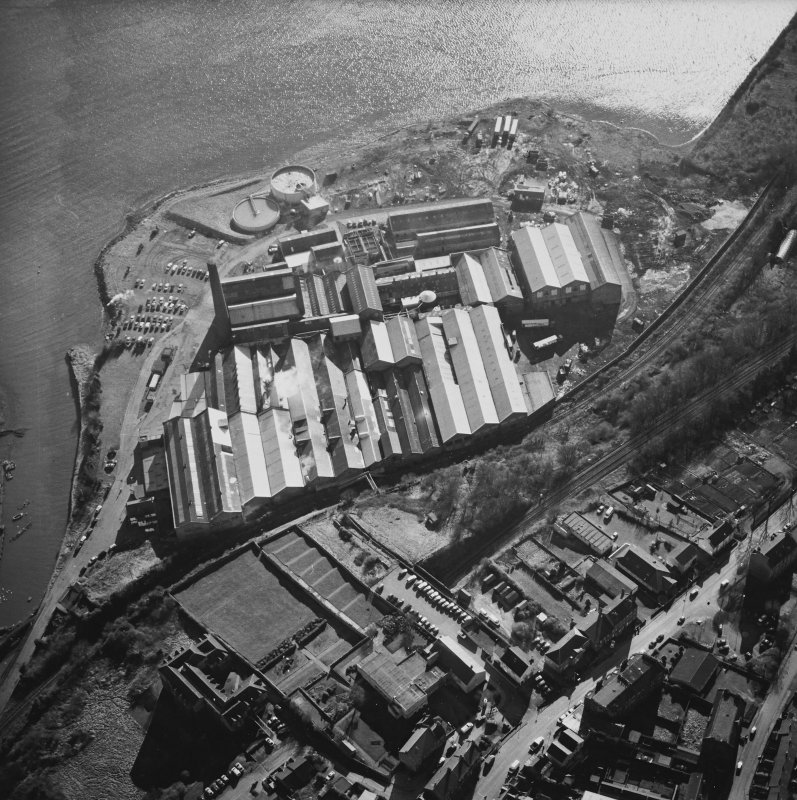 Oblique aerial view centred on the paper mill, taken from the N.