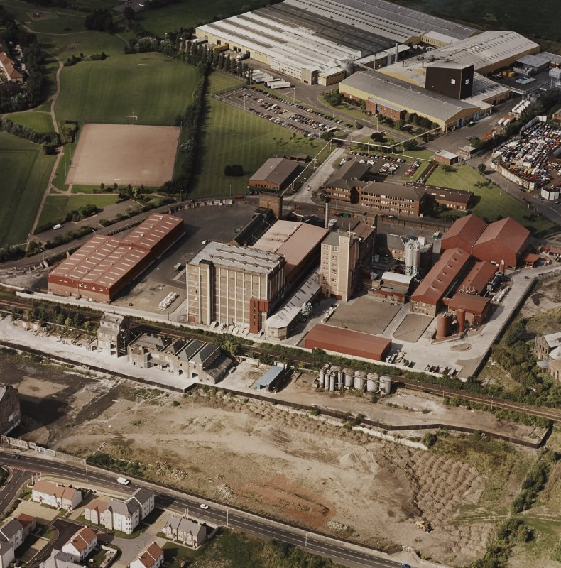 Oblique aerial view centred on the Linoleum works with offices adjacent, taken from the SE.