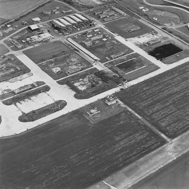 Oblique aerial view of Crail Airfield centred on the remains of the control tower, buildings, huts and aircraft hangars, taken from the SSE.