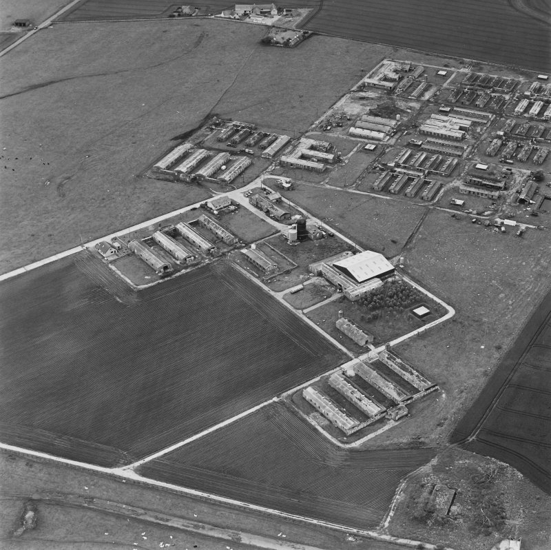 Oblique aerial view of Crail Airfield centred on the remains of buildings, a water tank and a hut, taken from the NNE.