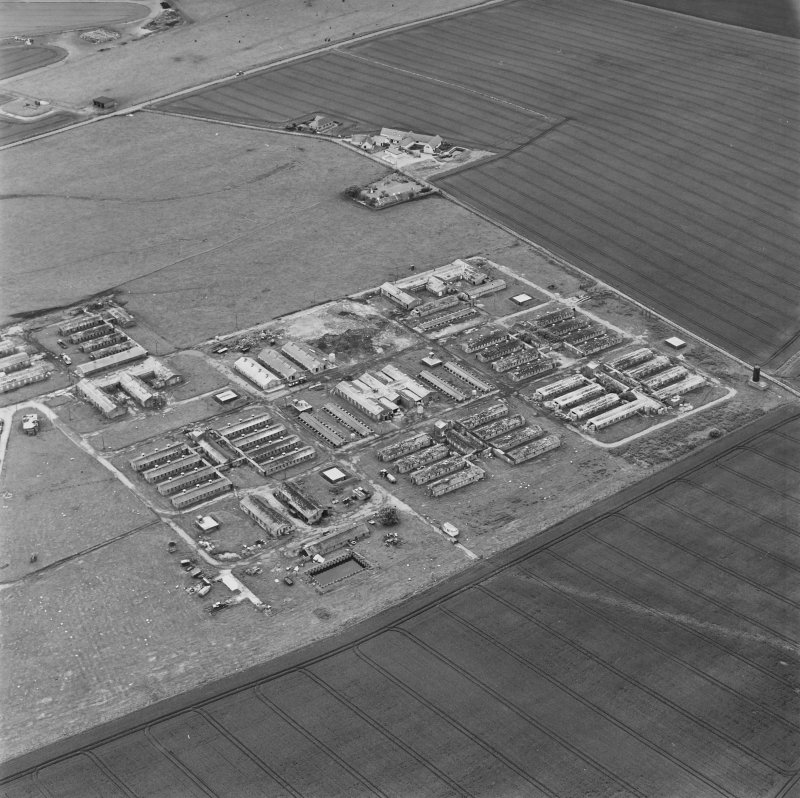 Oblique aerial view of Crail Airfield centred on the remains of buildings, a water tank and a hut, taken from the NNW.