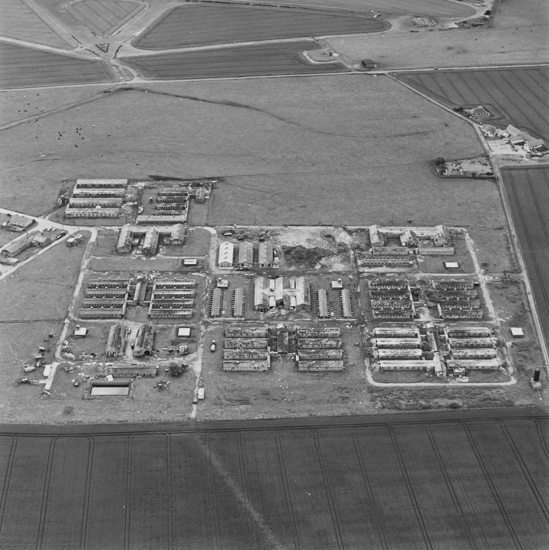 Oblique aerial view of Crail Airfield centred on the remains of buildings, a water tank and a hut, taken from the NW.