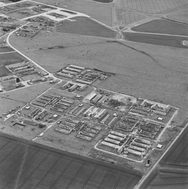 Oblique aerial view of Crail Airfield centred on the remains of buildings, a water tank and a hut, taken from the WNW.