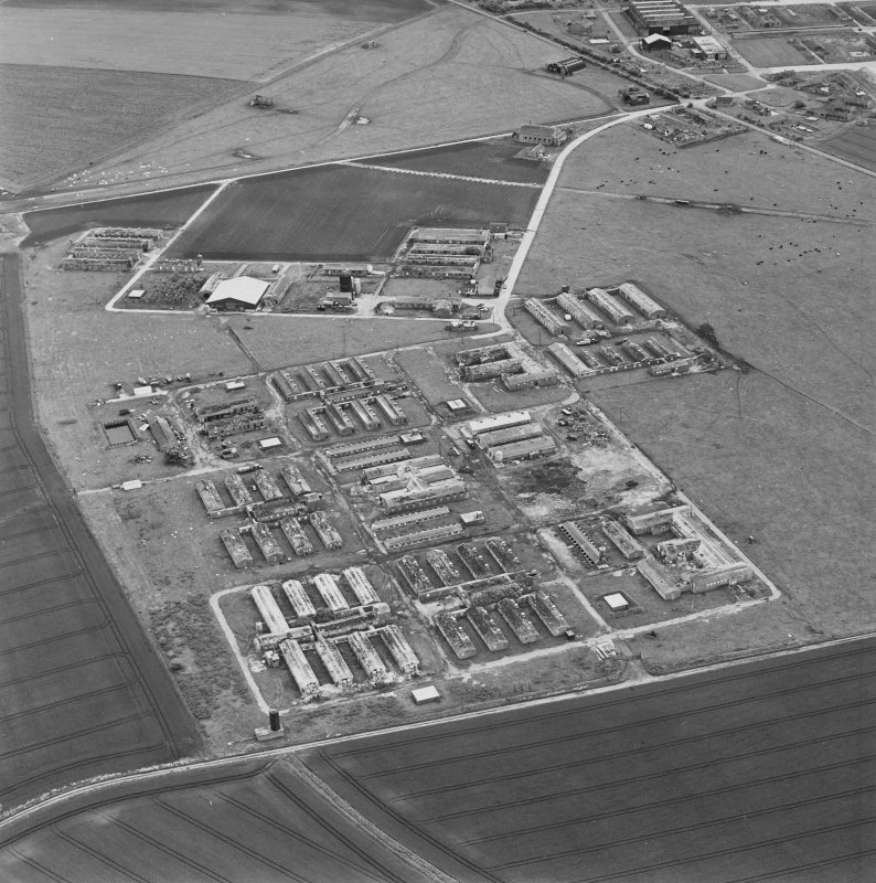 Oblique aerial view of Crail Airfield centred on the remains of buildings, a water tank and a hut, taken from the WSW.