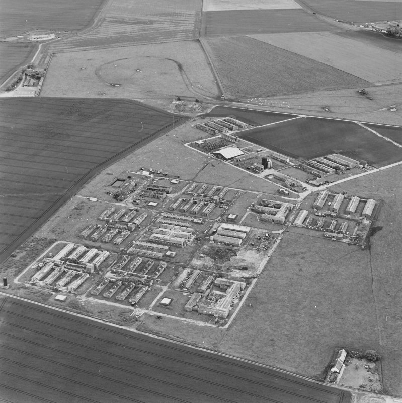 Oblique aerial view of Crail Airfield centred on the remains of buildings, a water tank and a hut, taken from the SSW.