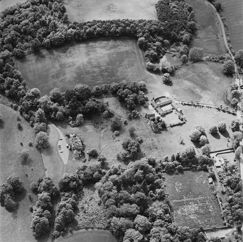 Oblique aerial view of Mountquhanie House centred on the country house, 'dovecot', stables and the remains of a castle, taken from the ENE.