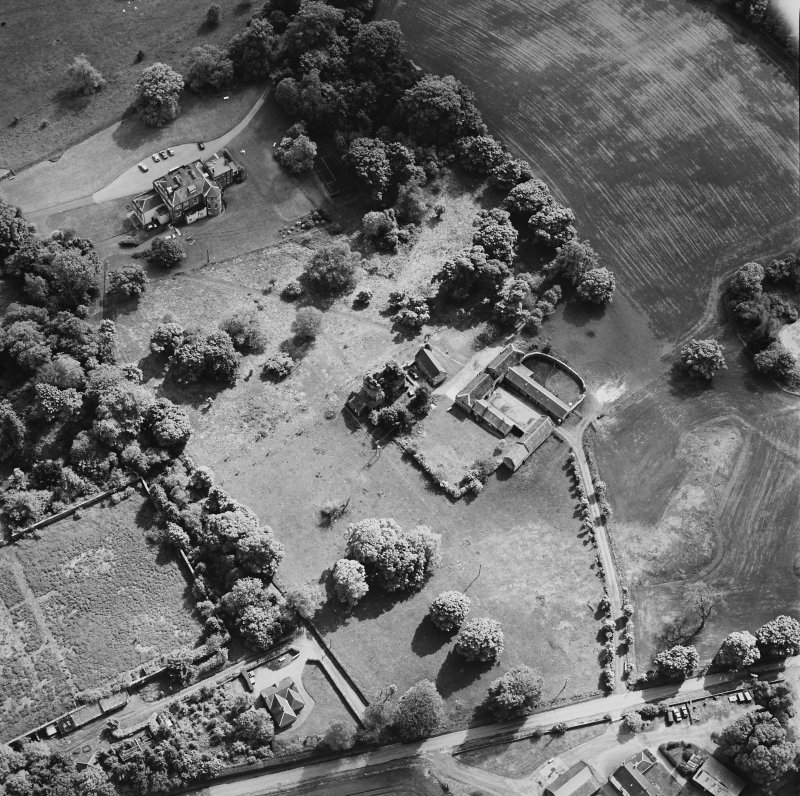 Oblique aerial view of Mountquhanie House centred on the country house, 'dovecot', stables and the remains of a castle, taken from the NNE.