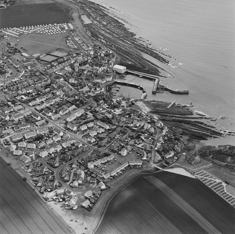 Oblique aerial view of St Monance centred on the village, harbour, church and burial ground, taken from the E.