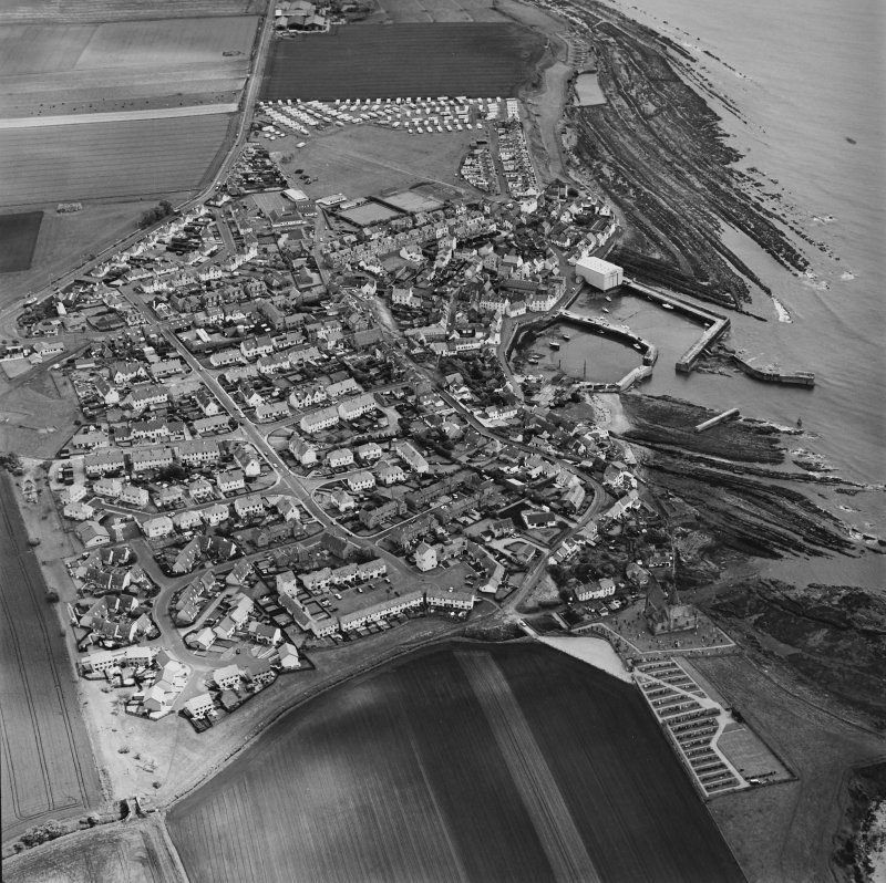 Oblique aerial view of St Monance centred on the village, harbour, church and burial ground, taken from the WSW.