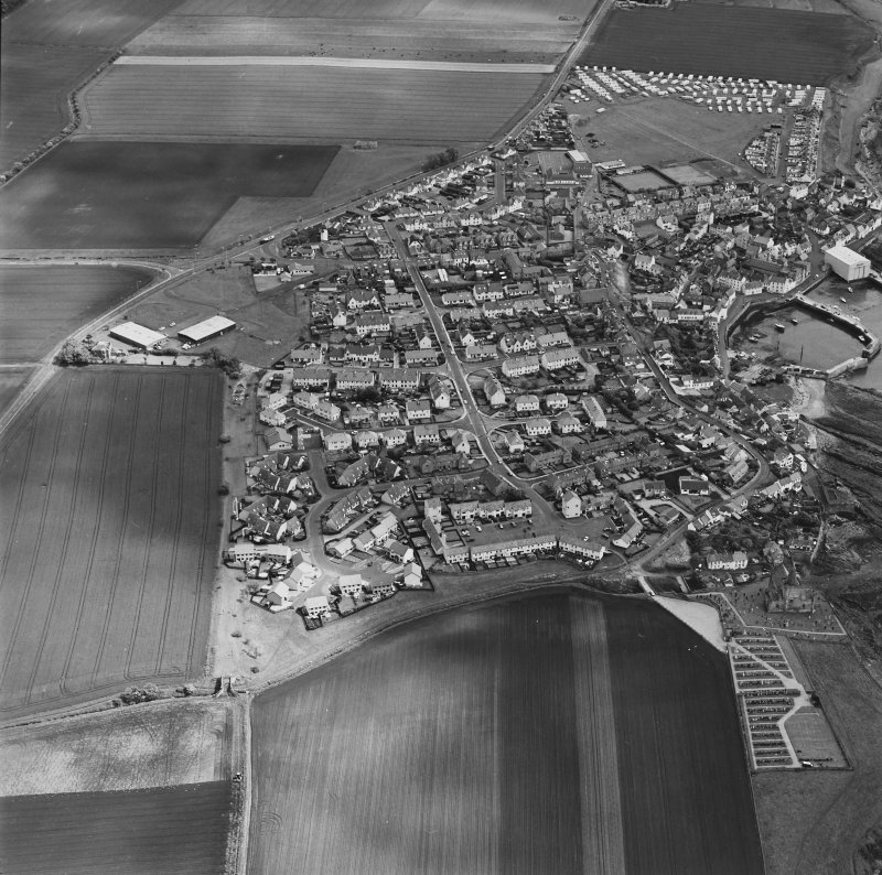 Oblique aerial view of St Monance centred on the village, harbour, church and burial ground, taken from the SW.