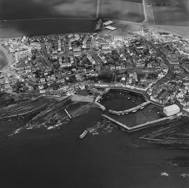 Oblique aerial view of St Monance centred on the village and harbour, taken from the SE.