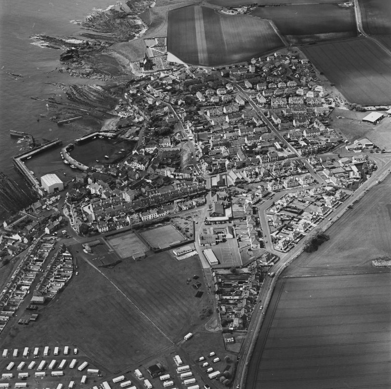 Oblique aerial view of St Monance centred on the village, harbour, church and burial ground, taken from the NE.
