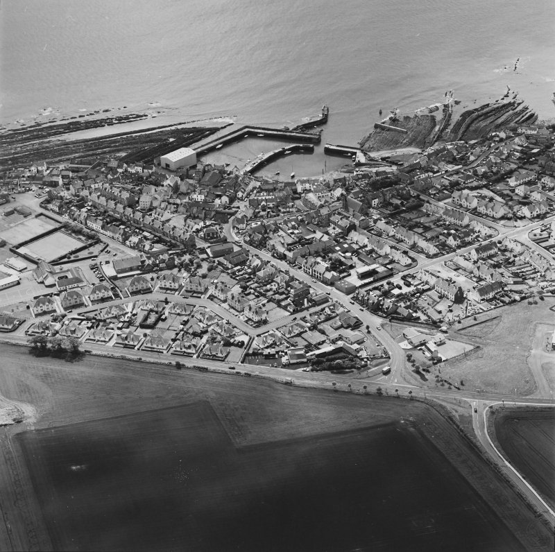 Oblique aerial view of St Monance centred on the village and harbour, taken from the NNW.