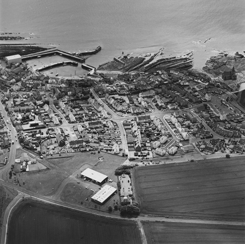 Oblique aerial view of St Monance centred on the village, harbour, church and burial ground, taken from the NW.