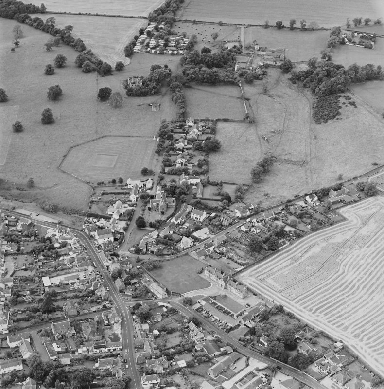 Oblique aerial view centred on the village of Upper Largo with walled garden, tower house and country house adjacent, taken from the ENE.