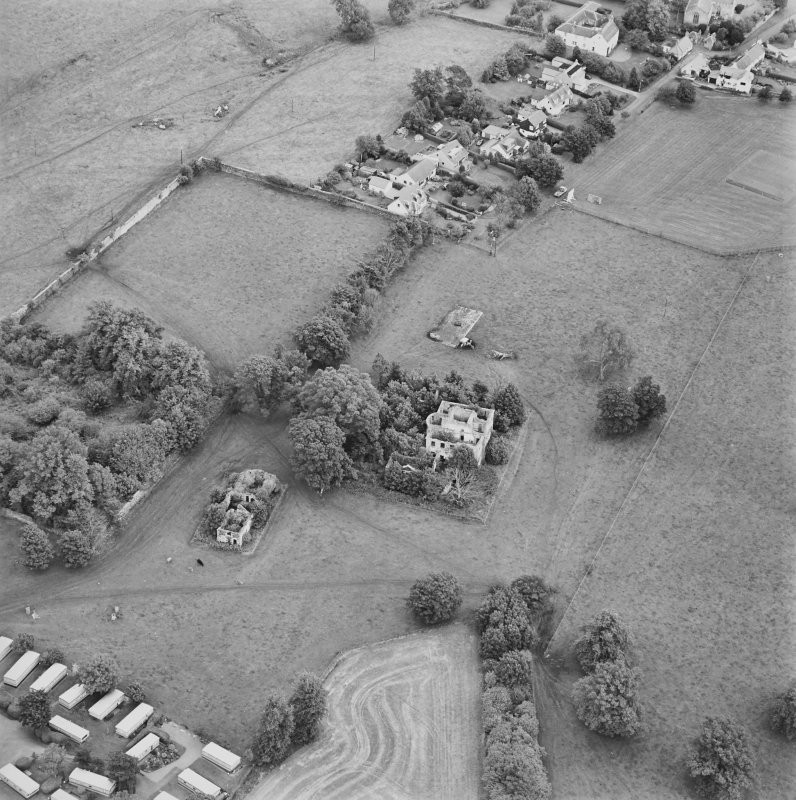 Oblique aerial view centred on the remains of the country house with stables and walled garden adjacent, taken from the WSW.